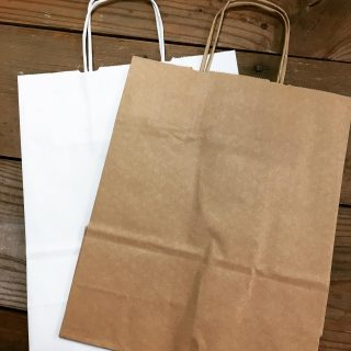 We have a vendor who sells these white/natural color kraft bags in bulk--350/case! And we have lovely tissue paper to go with them! Designs are: burgundy or black gingham, white solid, black crow, black star, stars & berries, sheep, and farmhouse! Bags are 8x4x10.5. Not open to the public